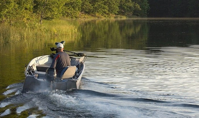 What should you do immediately if a boat motor catches fire