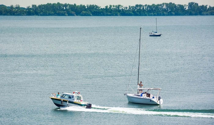 if another boat signals their intention to pass you from astern what should you do